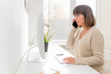 Charming Young Freelancer Woman Is Talking On Smartphone Working With Laptop From Home, Female Employee Has Pleasant Phone Conversation Working On The Distance, Connect With Customers By Mobile Phone.
