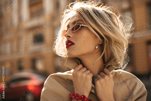Fotografía Blonde attractive young woman with red lips in colorful sunglasses touches collar of beige trench coat and poses outside