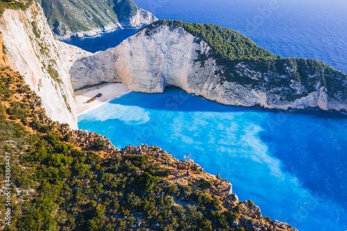 Aerial view of Navagio Beach - Shipwreck beach - on Zakynthos Island, Greece. Tourists on cliff edge enjoy view on summer travel trip