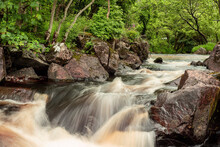 Small Water Cascade In A Green Forest. Nature Background. Water Flows In A Stream Between Brown Color Rocks. Nobody