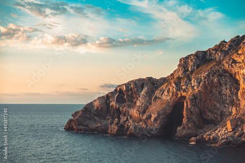 Fotografie, Tablou Amazing colorful sky sunrise above mountains cliffs and deep blue ocean
