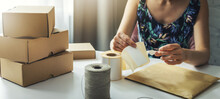 Small Online Business Owner Preparing Parcel Shipping Label At Home For Shipment Delivery. Banner