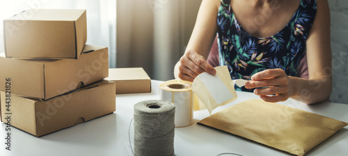 Tela small online business owner preparing parcel shipping label at home for shipment delivery
