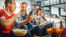 At Home Three Soccer Fans Sitting On A Couch Watch Sports Game On TV, Use Smartphone App To Online Bet, Celebrate Victory, Team Wins Championship. Friends Cheer, Enjoy Favourite Football Club Play