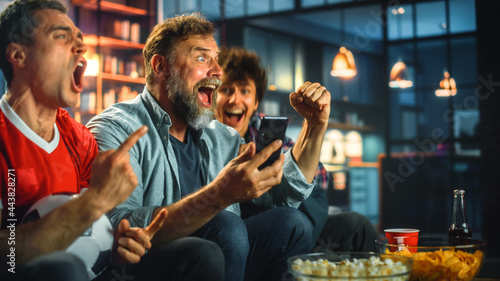 Photo Night at Home: Three Soccer Fans Sitting on a Couch Watch Game on TV, Use Smartphone App to Online Bet, Celebrate Victory when Sports Team Wins