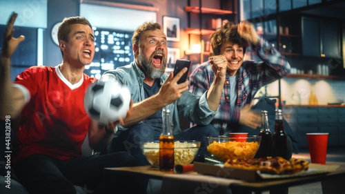 Canvas Print Night at Home: Three Soccer Fans Sitting on a Couch Watch Game on TV, Use Smartphone App to Online Bet, Celebrate Victory when Sports Team Wins