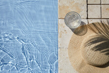 Summer Vacation. Hat On The Travertine Stone By The Beautiful Swimming Pool. Blue Sea Surface With Waves, Texture Water.