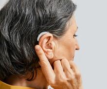 Hearing Aid Behind The Ear Of Senior Woman, Close-up
