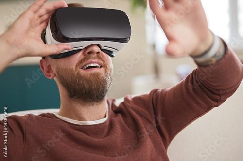 Fotografía Happy man in VR headset interacting with virtual world