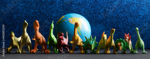 Foto Toy dinosaurs stand next to a globe on a blue background