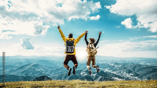 фотография Hikers with backpacks jumping with arms up on top of a mountain - Couple of youn