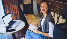 Happy Caucasian Female Writer Enjoying Creating Articles In Remote Job In Cafeteria Holding Notepad, Smiling Prosperous Businesswoman Freelancer Sitting Near Laptop Conputer With Mock Up Screen