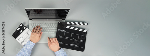 Fotografija Hands is typing and computer laptop or notebook with black clapperboard or movie slate on grey background