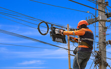 Low Angle View Of Technician On Wooden Ladder Is Installing Fiber Optic System In Internet Splitter Box On Electric Pole Against Blue Sky Background