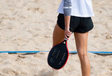 Fototapeta Kawa jest smaczna - Woman playing beach tennis on a beach. Professional sport concept