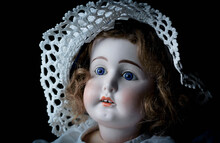 Face Of An Old, Antique Doll On A Black Background