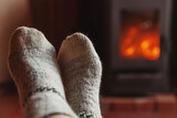 Fototapeta Kawa jest smaczna - Feet legs in winter clothes wool socks at fireplace background. Woman sitting at home on winter or autumn evening relaxing and warming up. Winter and cold weather concept. Hygge Christmas eve.