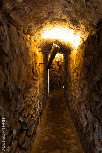 Slika na platnu Small passage illuminated by electric torches inside the ruins of an old medieva