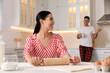 Leinwandbild Motiv Happy couple wearing pyjamas and spending time together in kitchen