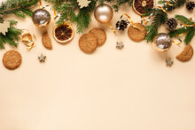 Christmas And New Year Holiday Background. Christmas Tree Branches, Christmas Balls And Cookies On Beige Background. Top View, Flat Lay, Copy Space