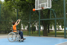 Disabled Teenage Boy In Wheelchair Playing Basketball  On Outdoor Court