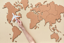 Woman Holding Plane Miniature Above Brown Map
