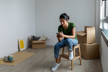 Indian Woman Texting With Her Phone At New Apartment