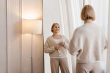 Mature Woman Buttoning Jacket Near Mirror