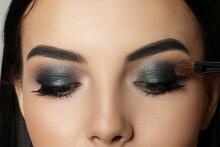 Applying Dark Eye Shadow With Brush Onto Woman's Face, Closeup. Beautiful Evening Makeup