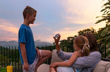 Family On Video Chat Call Outdoors With Mother Holding Smartphone