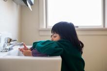 Girl Washing Hands In A Public Bathroom