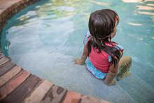 Girl Sitting On Side Of Pool