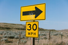 Bullet Holes Covering Arrow And Speed Limit Sign Along Rural Road