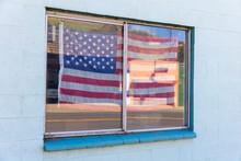 American Flag Hanging In Building Window