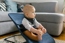 Portrait Of A Baby Sitting In A Chair Watching Cartoon