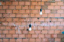 Light Bulbs Hanging On A Brick Wall