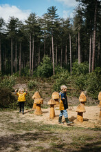 Siblings Walking Around Wooden Mushrooms In The Forest
