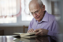 Hoary Pensioner Wearing Glasses Sitting At Table And Reading Book