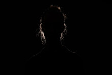Backlit Portrait Silhouette Of Unrecognizable Woman Hiding Face And Identy In The Dark Shadow