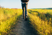 Active Tourist, A Man With A Briefcase In Nature, A Hipster In A Cap Is Walking Along A Path On A Green Hill, Healthy Lifestyle