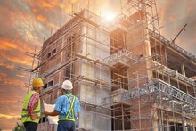 Construction Concept,a Team Of Engineers, Consultants, Project Managers, Contractors Working Together On The Construction Site Construction Workers Safety Suits And Helmet Planning Work With Blueprint
