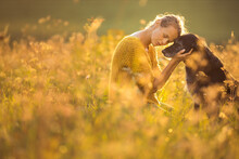 Pretty, Young Woman With Her Large Black Dog On A Lovely Sunlit Meadow In Warm Evening Light, Playing Together