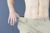 Slimming muscular man in pants that too big closeup