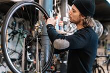 Mechanic Fixing Bicycle Wheel In Workshop