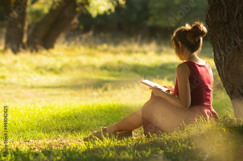 sunny portrait of a beautiful girl sitting on green glade under an arch of tree Fototapeta