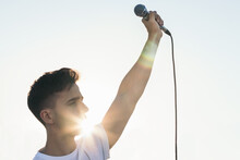 Singer With The Arm Raised Holding A Microphone With Sunlight Reflects