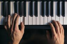 Man Hands Playing The Piano Close-up. Musical Keyboard