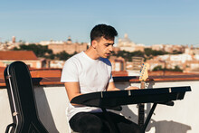 Side View Of A Man Playing Music Keyboard On A Rooftop