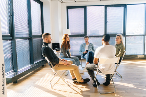 Fotografie, Obraz Multi-ethnic coworkers discussing working or personal issues together sitting in circle in light office room by window