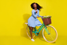 Full Body Photo Of Brunette Afro American Wear Red Headband Blue Dotted Dress Bike Send Air Kiss Isolated On Yellow Color Background